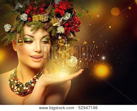 Christmas Winter Woman with Miracle in Her Hand. Fairy. Beautiful New Year and Christmas Tree Holiday Hairstyle and Make up. Magic. Beauty Fashion Model Girl over Holiday Blinking Background.