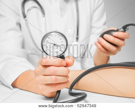Doctor measures blood pressure by sphygmomanometer
