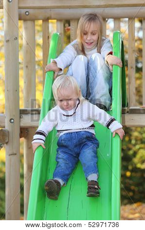 Funny kids playing on the chute.