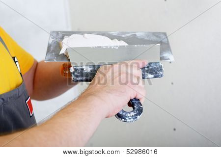 repairman works with plasterboard, preparing plaster for plastering dry-stone wall, home improvement poster