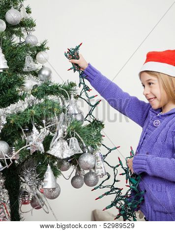 Happy girl decorating Christmas tree with fairy lights at home