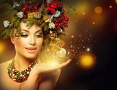 Christmas Winter Woman with Miracle in Her Hand. Fairy. Beautiful New Year and Christmas Tree Holiday Hairstyle and Make up. Magic. Beauty Fashion Model Girl over Holiday Blinking Background.  poster