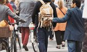 Young man taking wallet from backpack of a man walking on street during daytime. Pickpocketing on the street during daytime poster