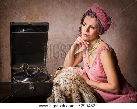 Vintage 1920s style lady in pink listening to an antique record player