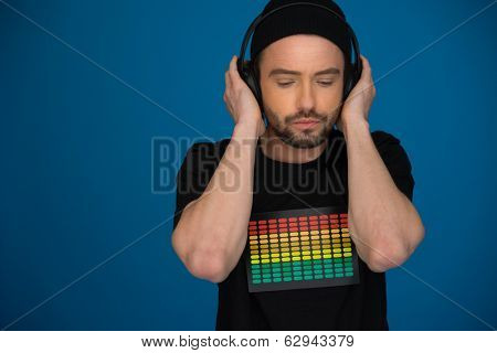 handsome Male DJ with headphones on blue background