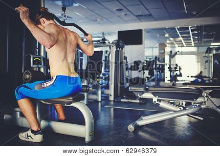 Young man sitting in gym and training on special sport equipment