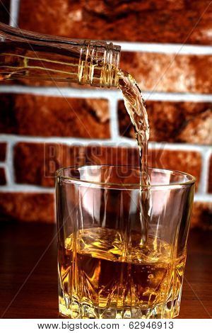 Luxury old whiskey glass on brick wall background