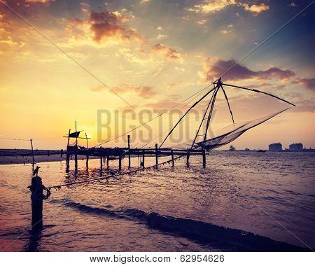 Vintage retro hipster style travel image of Kochi chinese fishnets on sunset. Fort Kochin, Kochi, Kerala, India