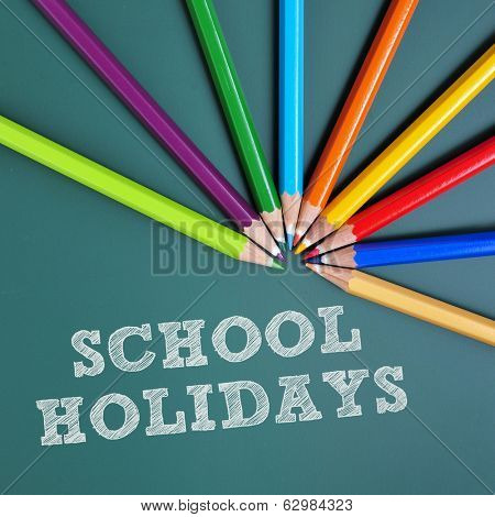 coloured pencils of different colors and text school holidays writtten in a green chalkboard