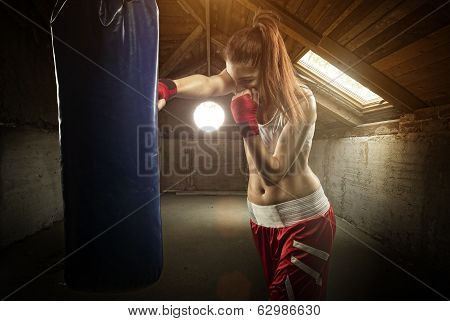 Young women boxing hitting the boxing bag - on the attic
