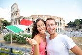 Italy travel couple with Italian flag by Colosseum embracing. Happy tourists lovers on honeymoon sightseeing having fun in front of Coliseum. Love and tourisn concept with multiracial couple. poster