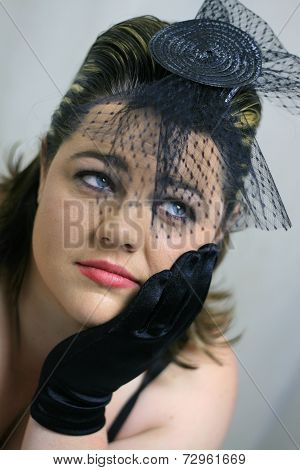 A lady wearing a black fascinator and gloves (hand to her face) looking off camera with a not so fascinated expression. poster