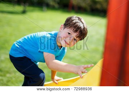 Little Boy Climbing On Slide