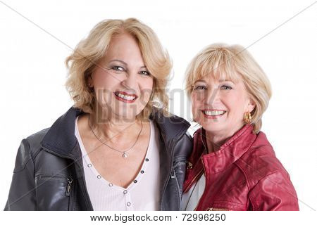 Two Caucasian older women in pension smiling at the camera.