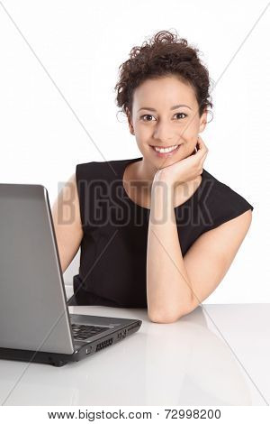 Young isolated business woman sitting at desk with lap top resting face on hand on white background