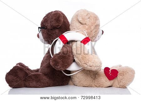 Friends help:  teddy bears back to back giving support isolated on white background - also concept for teamwork or partnership