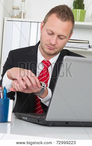 Businessman looking at watch with laptop - end of work