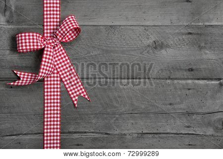 Grey wooden background with red and white checkered bow as border