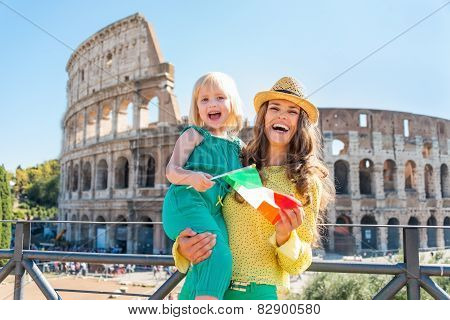 Happy Mother And Baby Girl With Italian Flag In Front Of Colosse