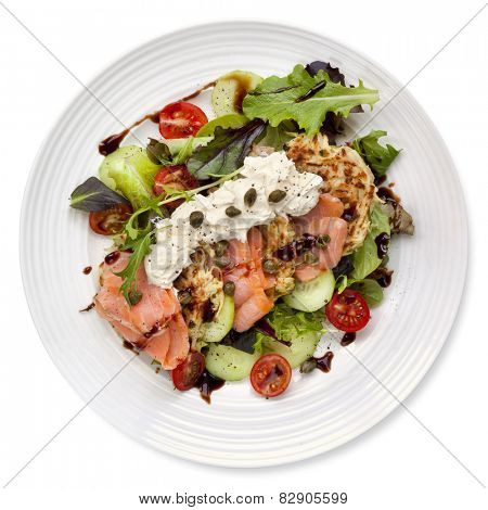 Smoked salmon salad with potato rosti and creme fraiche.  Overhead view, isolated on white.
