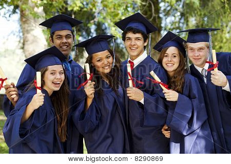 Graduating Students Smiling And Laughing With Diplomas