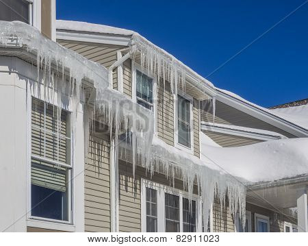 Ice dams and snow on roof and gutters after bitter cold in New England, USA poster