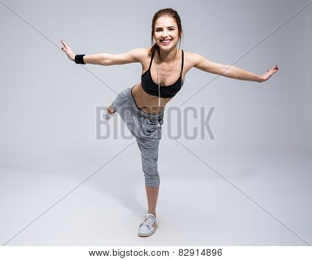Smiling sports woman doing excersises over gray background