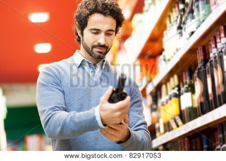 Young man choosing a bottle of red wine