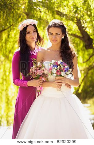 Cute Bride Posing With Bridesmaid At Park At Sunny Day