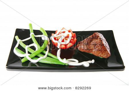 Fillet Mignon On A Black Plate With Tomato