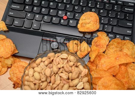 Close Up Of Open Laptop With Chips Scattered On Keyboard And Dice Skull