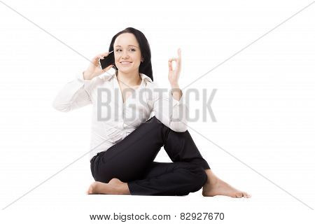 Young Business Woman In Yoga Pose Talking On Mobile Phone On White Background