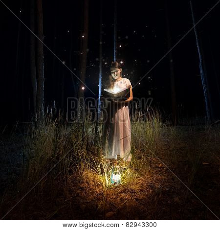 Woman In Long Dress Reading Big Old Book At Mysterious Forest With Fireflies