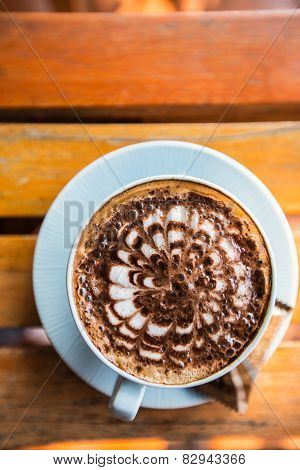 A cup of mocca stands on  wooden table