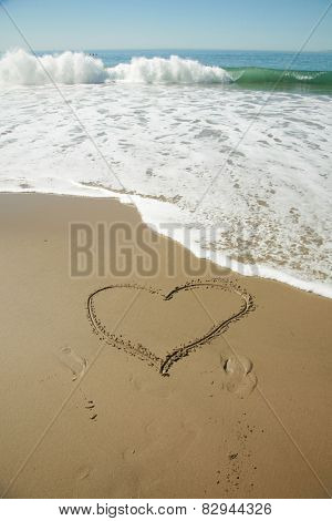 A heart drawing in the sand in Laguna Beach California. The ocean waves gently wash away part of the heart with its gentle action of the ever present tide. Romance is alive and love is here to stay.
