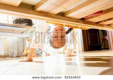Little Smiling Girl Looking Under Bed