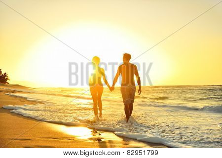 Honeymoon romantic couple in love holding hands walking on beautiful sunset at beach in waterfront. Lovers or newlywed married young couple by the sea enjoying relaxed vacation travel holiday. Hawaii.