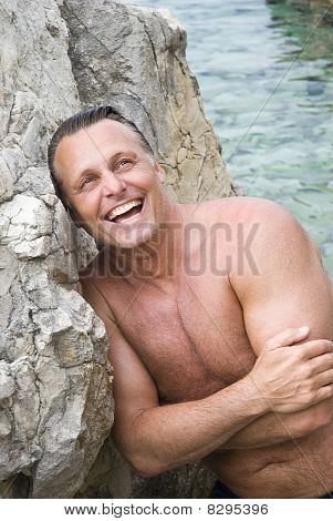 Happy smiling forties man leaning on a rock at the beach