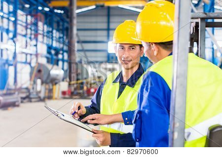 Worker and forklift driver in industrial factory looking at camera