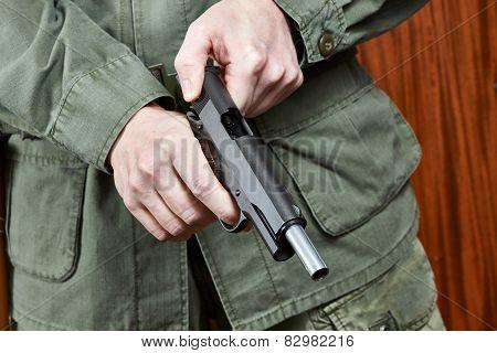 The soldier shutter cocking a pistol gun poster