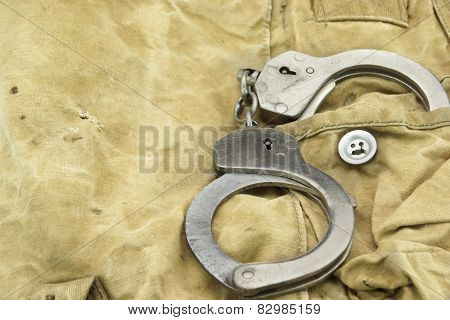Handcuffs in The Camouflage Army Pants Pocket or Haversack or Bag or Fabric. Background and Texture. poster
