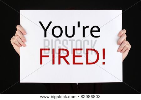Sheet of paper with text You're Fired in hands isolated on black