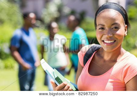 pretty female african college student holding books on campus