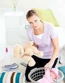 Depressed young mother putting toy into a basket in the lving room poster