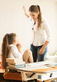Portrait of angry mother hitting intimidated daughter poster