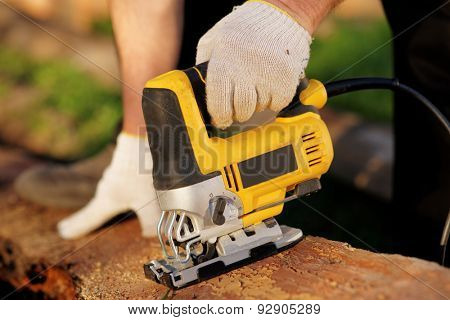 Carpenter is cutting wood with fret saw, outdoor shot, reality shot