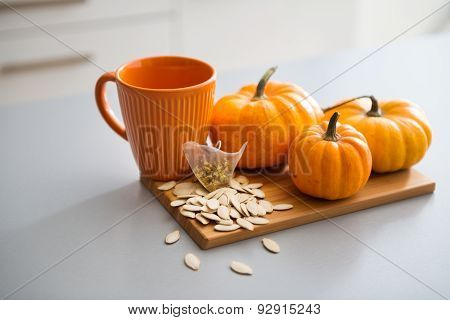 A Study In Pumpkin Colours Including A Mug, Seeds, And Pumpkins
