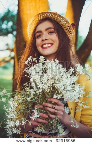 Hipster fashion girl in straw hat keep beauty flowers on hands poster