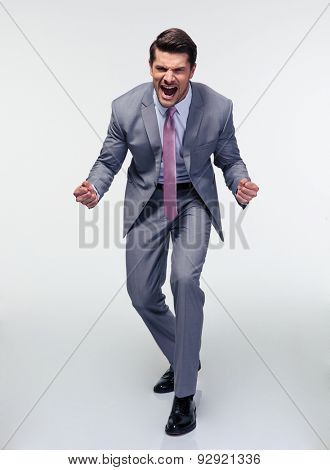 Full length portrait of angry businessman shouting over gray background