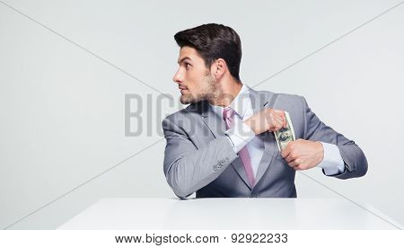 Young businessman sitting at the table and putting money in pocket over gray background. Looking away